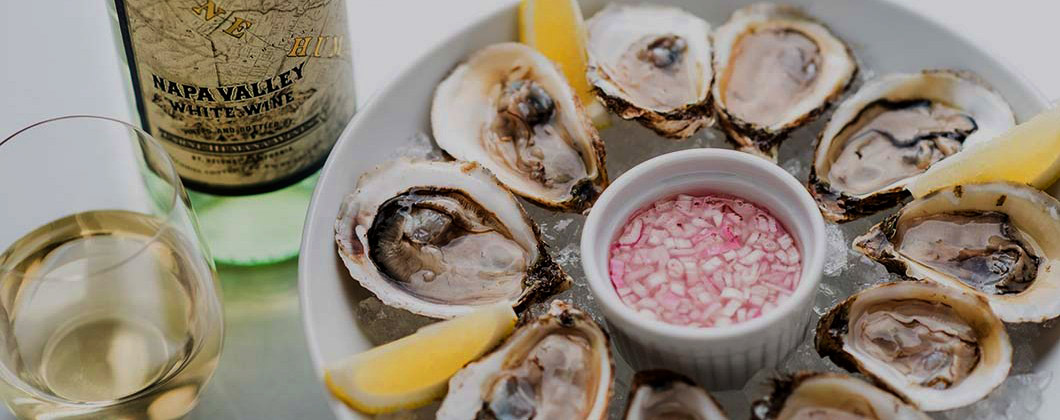 A plate of fresh oysters with red wine vinegar mignonette - Carne Humana white wine and wine glass