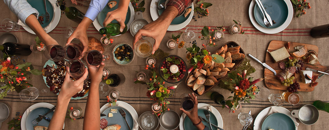 Aerial table shot of a havest table - people clinking wine glasses atop assorted appetizers